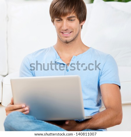 happy man sitting on the sofa working with notebook