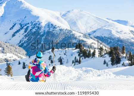 Happy man sitting on top of Alps, resting after skiing against wonderful winter mountains background - stock photo