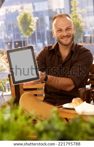 Happy man sitting outdoors, holding tablet computer with blank screen, smiling, looking at camera. - stock photo