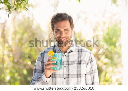 Happy man smiling at camera with drink on a sunny day - stock photo