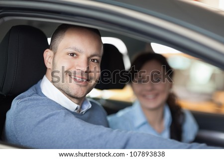 Happy man smiling in a car with a woman