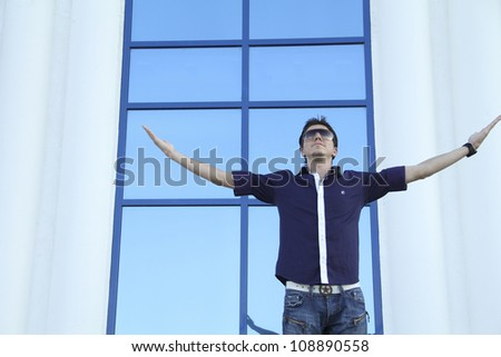 Happy man stand and expressing success and victory concept,  in front of a building - stock photo