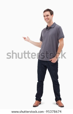 Happy man standing and presenting something behind against white background - stock photo