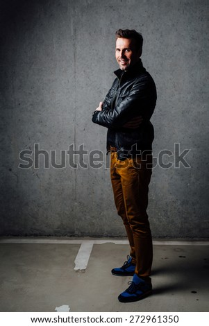 Happy man standing in underground garage wearing leather jacket