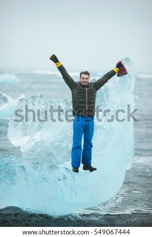 happy man standing on big ice block in Iceland