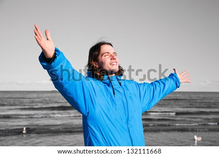 Happy man standing on the beach with hands up on black and white seascape. Concepts like overcoming depression etc.