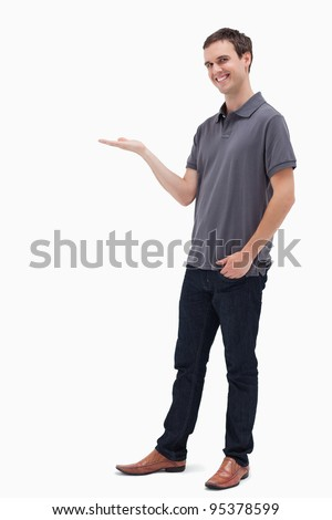 Happy man standing while presenting against white background - stock photo