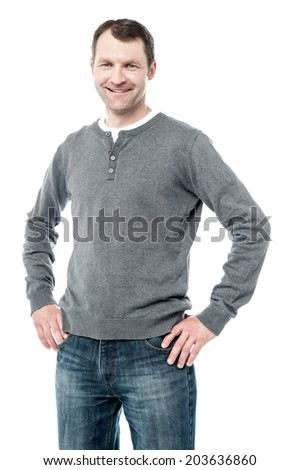 Happy man standing with hand on hips wearing casual clothes - stock photo