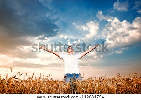 Happy man standing with open arms on a wheat field - stock photo