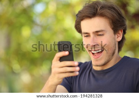 Happy man surprised looking at the smart phone with a green background - stock photo