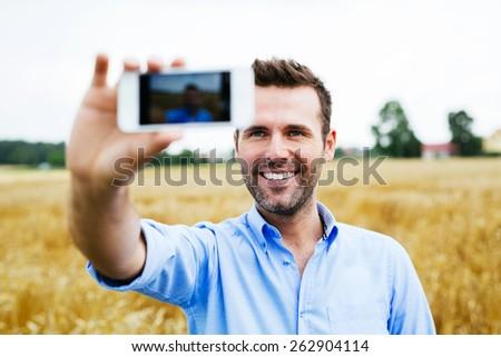 Happy man taking selfie in a field - stock photo