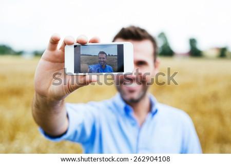 Happy man taking selfie in a field, blurred background - stock photo