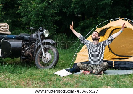 Happy man taking sunbath in forest near the camping and motorcycle with sidecar. Relaxation, yoga practicing, unity with nature concept.