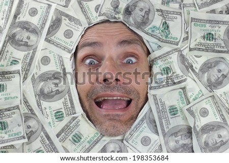 happy man under a bed of dollar notes - stock photo