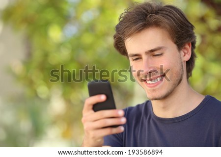 Happy man using a smart phone outdoor with a green background - stock photo