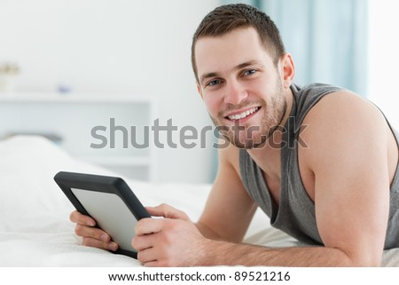 Happy man using a tablet computer while lying on his belly in his bedroom - stock photo