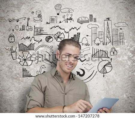 Happy man using a tablet with sketches  - stock photo