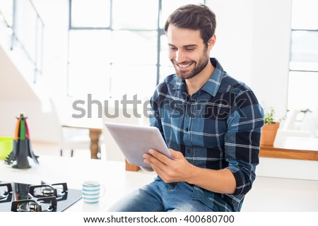 Happy man using digital tablet in kitchen at home - stock photo