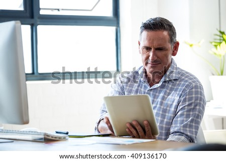 Happy man using digital tablet in office - stock photo