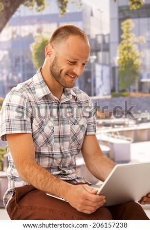 Happy man using laptop computer, sitting outdoors, smiling.