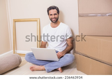 Happy man using laptop surrounded by boxes in his new home - stock photo