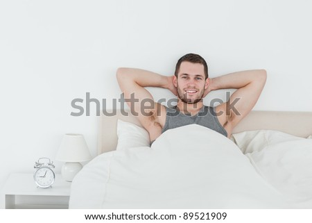 Happy man waking up in his bedroom - stock photo