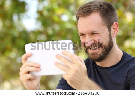 Happy man watching videos in a ereader tablet in a park with a green background - stock photo