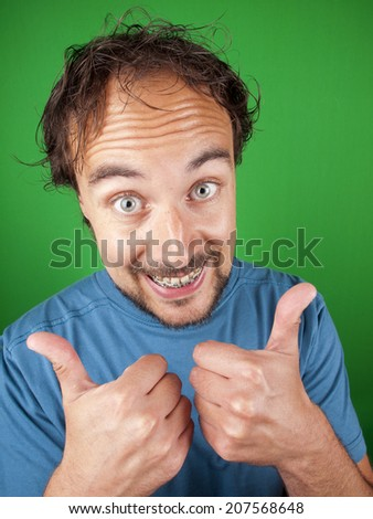 Happy man with a beard and braces putting his thumbs up for you over a green background - stock photo