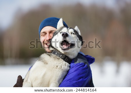 Happy man with a husky at winter time - stock photo