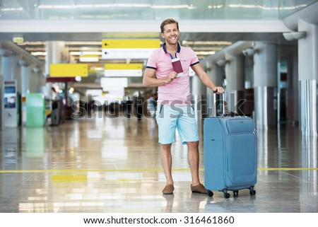 Happy man with a suitcase at the airport - stock photo