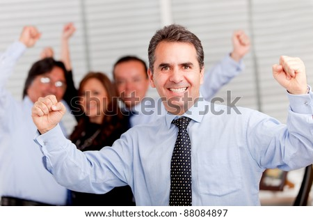 Happy man with arms up leading a successful business group - stock photo
