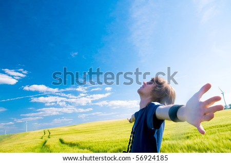 Happy man with arms up on summer lanscape - stock photo
