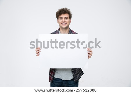 Happy man with curly hair holding blank billboard - stock photo