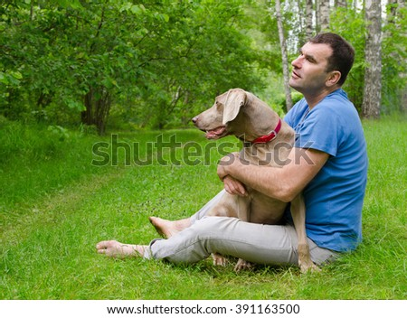 Happy man with  dog outdoors - stock photo