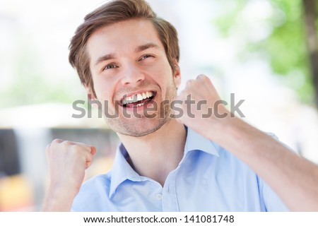 Happy man with fists clenched - stock photo