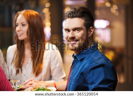 happy man with friends having dinner at restaurant