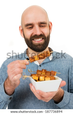 happy man with grilled tofu sticks - stock photo