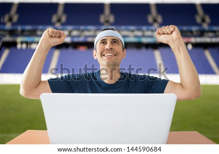 Happy man with hands raised in the air after winning a sports bet in stadium - stock photo