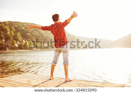 Happy man with hands up on sunset. Open arms, standing on a pier barefoot. Enjoying sun. Gazing sun.    - stock photo