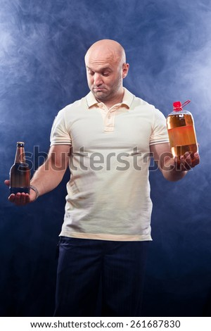 happy man with lots of beer in confusion on a black background - stock photo