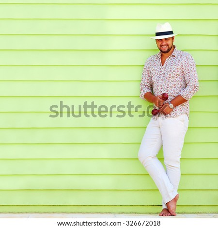happy man with maraca playing music near the colorful wall - stock photo