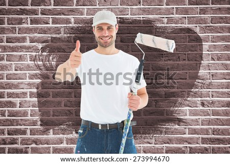 Happy man with paint roller gesturing thumbs up against red brick wall - stock photo