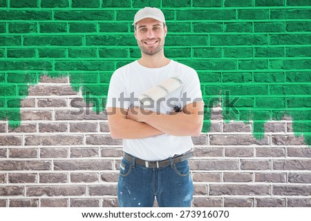 Happy man with paint roller standing arms crossed against red brick wall - stock photo