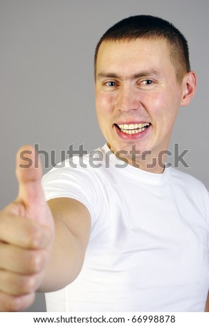 Happy man with thumbs up isolated on gray.