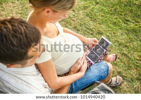 Happy man with woman pregnant on nature in summer