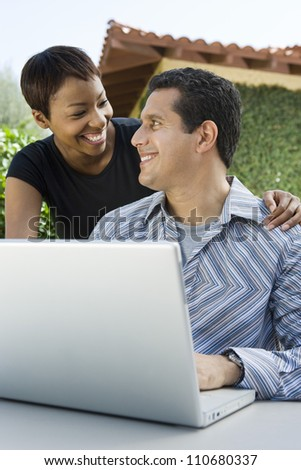 Happy man with woman working on laptop