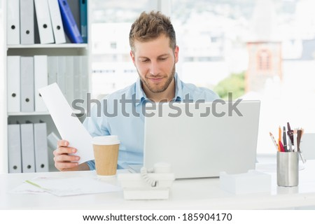 Happy man working at his desk on laptop in creative office - stock photo