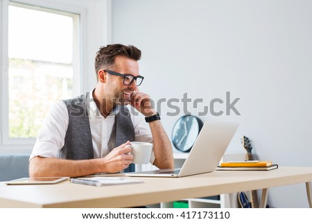 Happy man working on laptop and drinking coffee at home - home of - stock photo