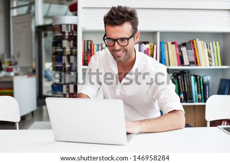 Happy man working on laptop in library - stock photo