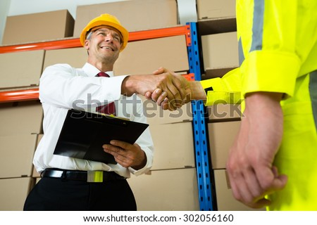Happy Manager Holding Clipboard Shaking Hands With Warehouse Worker - stock photo